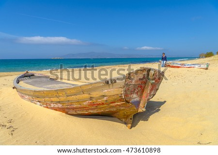 Abandoned fishing boat on one of the most beautiful beaches in the world in Naxos island, Cyclades, Greece.
