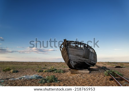 Abandoned fishing boat on shingle beach landscape at sunset