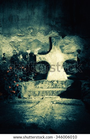 Abandoned grave at dark spooky night on an old cemetery. Tombstone cross next to the ruined church wall. Evil and death concept - stock photo