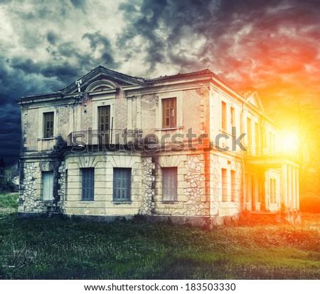 Abandoned haunted house with dramatic sky - stock photo