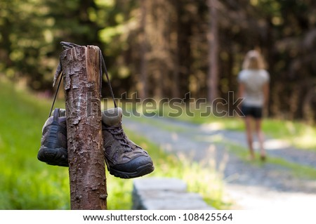 Abandoned hiking shoes with a woman walking bare feet - stock photo