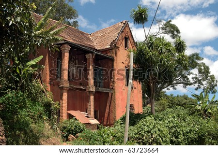 Abandoned home in Madagascar: old colonial style house in ruins with plants growing everywhere around it. - stock photo