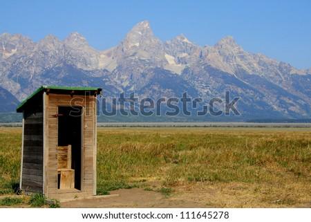 Abandoned homesteader's outhouse, Grand Teton National Park, Jackson Hole, Wyoming, with Teton range in background. - stock photo