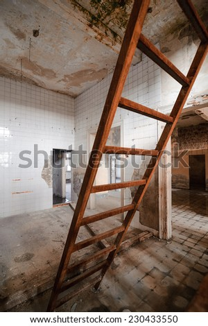 Abandoned house and old dingy step ladder access to loft - stock photo