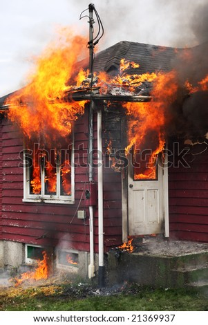 Abandoned house burning, with flames through windows and door
