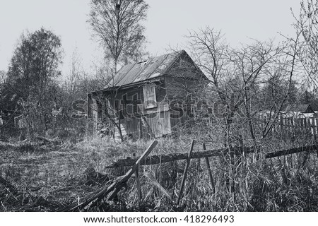 Abandoned house. Old garden plot. A broken fence. poor housing. poverty. rustic. black and white image.