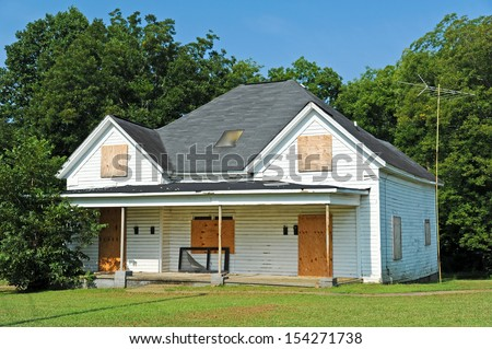 Abandoned House with Boarded up Windows and Doors - stock photo