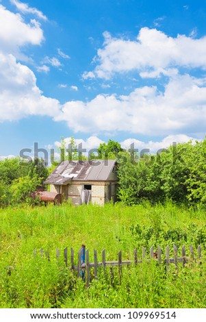 Abandoned hut among trees and bushes in summertime - stock photo