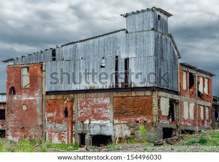 abandoned industrial building constructed of red bricks on crisis time - stock photo