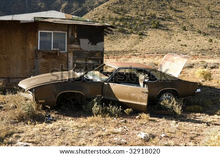 Abandoned Junk Car in Desert next to House - stock photo