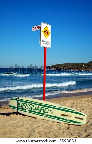 abandoned lifeguard surf, sign 'dangerous current', blue clear sky - stock photo