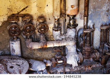Abandoned machine of rusty pipes and dirty valves with interesting natural lighting: warm sunlight on left top from outdoor, the right bottom from cold basement. - stock photo