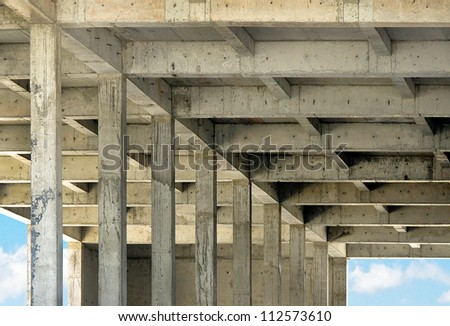 Abandoned modern construction - empty house at blue sky background. Reinforced concrete structure of the upper floors of building under construction - supporting columns and galleries empty space. - stock photo