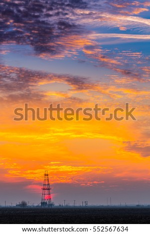 Abandoned oil and gas rig profiled on dramatic evening sky