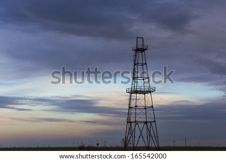 Abandoned oil and gas rig profiled on sky