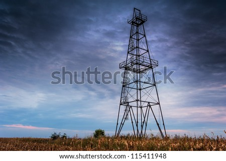 Abandoned oil rig, dramatic clouds and evening sky - stock photo