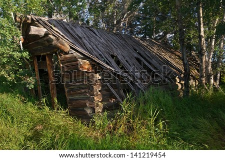 Abandoned old log cabin rotting in the forest - stock photo