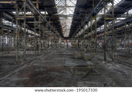 Abandoned old production hall with many plants and steel posts - stock photo