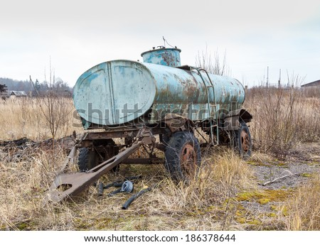 abandoned old rusty car trailer tank in the field - stock photo
