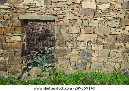 Abandoned old schist house in an European rural area. Facade wall, backgrounds and textures - stock photo