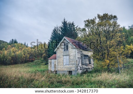 abandoned old wooden building in the woods - stock photo