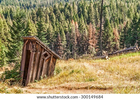 Abandoned outhouse in a meadow near a forest looks like it is sinking - stock photo
