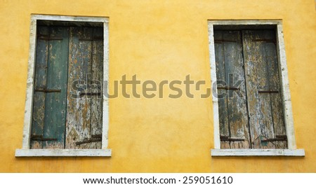 Abandoned palazzo in Venice (Italy). Ocher stucco wall and closed wooden shutters with peeling paint. - stock photo