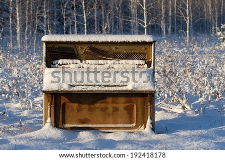 Abandoned Piano in Winter Field - upright piano that has been abandoned in a snowy winter field / meadow. - stock photo