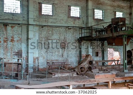 Abandoned plant interior with rusty metal equipment and cyan brick wall - stock photo
