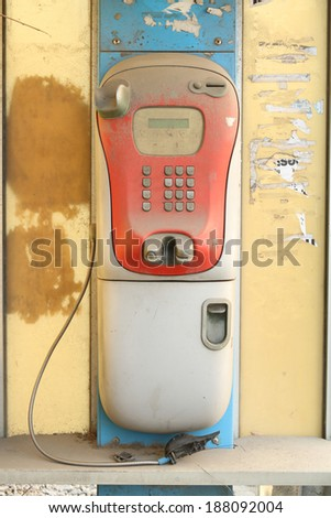 Abandoned public telephone, damaged and dirty