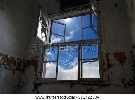 Abandoned room interior with broken window - stock photo