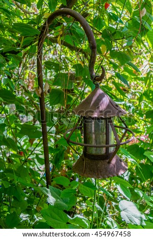 abandoned rusty street lamp hidden in foliage with cylinder shade
