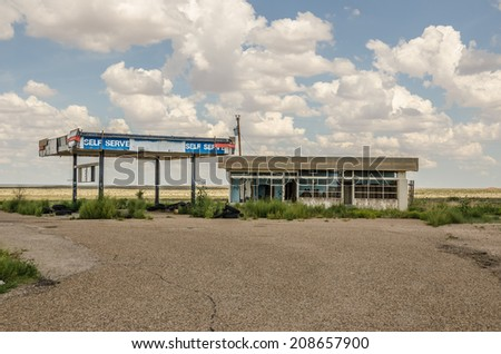 Abandoned service station on Route 66 with a few tires laying around.  The gas pumps are long gone as are the windows. - stock photo