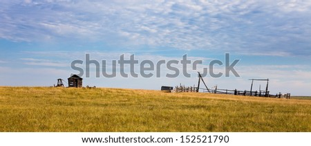 Abandoned shack and corral in a grassy field - stock photo
