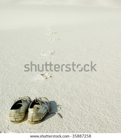 Abandoned shoes on white sand leaving footprints going infinitely