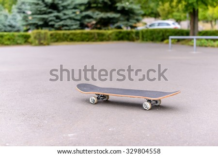 Abandoned skateboard at a skate park standing in the center of the tarmac with trees and a car visible in the distance