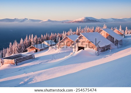 abandoned snow-covered hut (cabins) in the mountains at sunrise - stock photo
