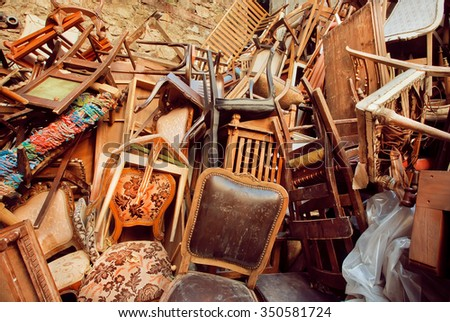 Abandoned store with old wooden chairs, one on the other, thrown into the street  - stock photo