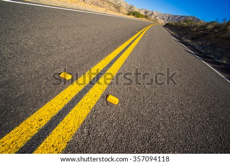 Abandoned stretch of new asphalt road in the Mojave Desert of California. - stock photo