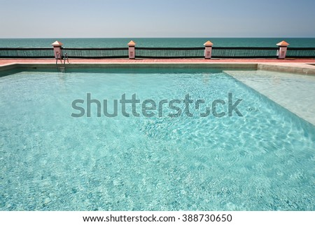Abandoned swimming pool by the sea. - stock photo