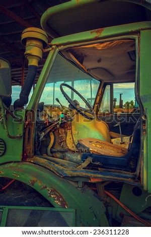 Abandoned Tractor Cab. Tractor is specifically designed to deliver a high tractive effort at slow speeds, for the purposes of hauling a trailer or machinery used in agriculture or construction. - stock photo