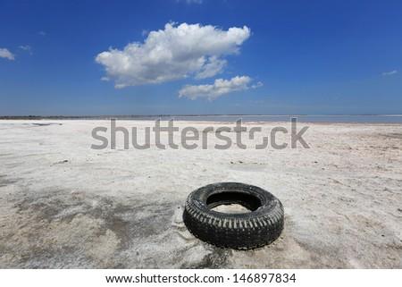 Abandoned tyre on salt sea shore - stock photo