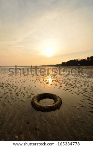 Abandoned tyre on the beach when the sun goes down - stock photo