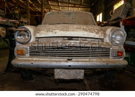 Abandoned vintage car covered with layer of dust in the shed - stock photo