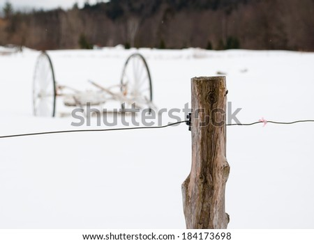 Abandoned wagon in a snowy field behind barbed wire and wooden post - stock photo