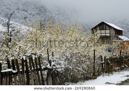 Abandoned wooden house with old broken fence in winter, Armenia, Caucasus mountains,Asia - stock photo
