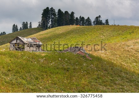 Abandoned wooden hut in a highland - stock photo