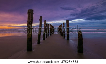 Abandoned wooden piles in St. Clair Beach in Dunedin during sunrise.