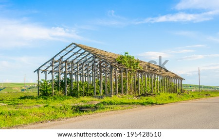 Abandoned wrecked and ruined agriculture structure still standing on farmland made of concrete and steel beams suggesting good building and engineering - stock photo
