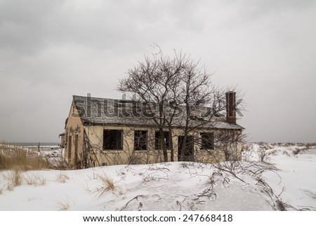 Abandoned yellow house in snow. - stock photo